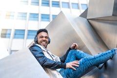 Inconformista hermoso Guy Listening Music en los auriculares y la sonrisa foto de archivo