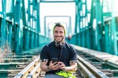 Inconformista hermoso Guy Using el tel?fono m?vil y los auriculares que llevan El sentarse en las v?as del tren fotos de archivo libres de regalías