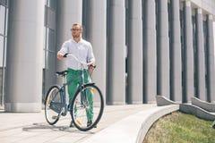 Inconformista hermoso que disfruta de paseo de la ciudad en bicicleta Imagen de archivo
