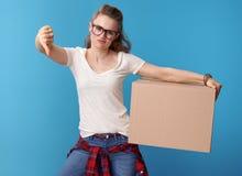 Inconformista infeliz con la caja de cartón que muestra los pulgares abajo en azul Foto de archivo
