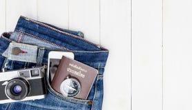 Inconformista Jean con los objetos del viaje y equipo en la madera Fotos de archivo libres de regalías
