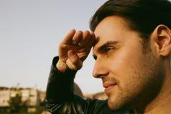 Inconformista joven en una chaqueta de cuero negra que mira lejos en ciudad borrosa en fondo horizontal Retrato del primer Foto de archivo
