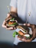 Inconformista joven que sostiene las hamburguesas vegetarianas del queso de soja de la zanahoria Foto de archivo