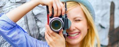 Inconformista joven que toma la foto con la cámara retra de la foto Foto de archivo libre de regalías