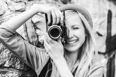 Inconformista joven que toma la foto con la cámara retra de la foto Foto de archivo