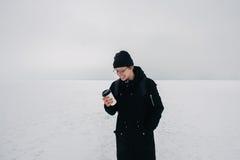 Inconformista joven sonriente del individuo en negro en la charca congelada nevada blanca con una taza de café Imagen de archivo libre de regalías