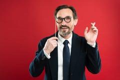 Inconformista o empollón El hombre sostiene las lentes de los apoyos del partido Boss o el hombre de negocios lleva el traje form foto de archivo