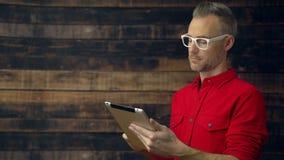 Inconformista pensativo en camisa roja usando la tableta metrajes