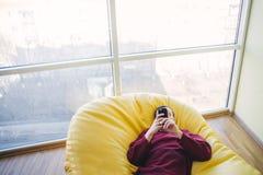 Inconformista que descansa en una mala silla El hombre joven es y utiliza smartphone Oficina moderna Hombre en interior moderno Foto de archivo