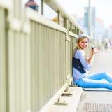 Inconformista que se sienta en la calle de la ciudad con la cámara retra de la foto Imágenes de archivo libres de regalías