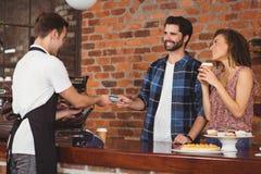 Inconformista sonriente que da la tarjeta de crédito al barista Fotografía de archivo