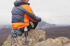 Inconformista - un escalador en abajo una chaqueta y un casquillo hecho punto se sienta y descansa sobre el top de una roca Imágenes de archivo libres de regalías