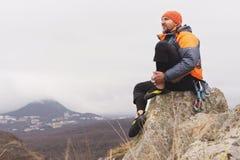 Inconformista - un escalador en abajo una chaqueta y un casquillo hecho punto se sienta y descansa sobre el top de una roca Imagen de archivo