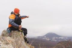Inconformista - un escalador en abajo una chaqueta y un casquillo hecho punto se sienta y descansa sobre el top de una roca Fotos de archivo