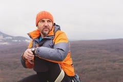 Inconformista - un escalador en abajo una chaqueta y un casquillo hecho punto se sienta y descansa sobre el top de una roca Foto de archivo