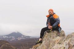 Inconformista - un escalador en abajo una chaqueta y un casquillo hecho punto se sienta y descansa sobre el top de una roca Fotografía de archivo