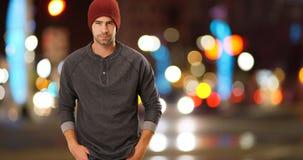 Inconformista urbano atractivo que se coloca al lado de la calle en la noche Imagenes de archivo