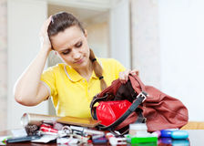 Inconsiderate woman lost something  in  purse. Upset inconsiderate woman lost something  in her purse Royalty Free Stock Photos