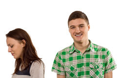 Inconsiderate young man. Inconsiderate unfeeling handsome young men smiling with pleasure as his girlfriend turns aside in tears upset at his oblivious attitude Stock Photography