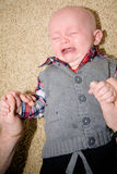 Inconsolable Crying Baby. Baby crying with mouth open and eyes closed while his father tries to calm him down. His gums and tongue are visible Royalty Free Stock Images
