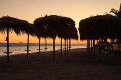 Incontrarsi un nuovo giorno all'alba sulla riva di un mare calmo nella sabbia Immagine Stock