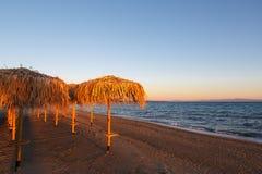 Incontrarsi un nuovo giorno all'alba sulla riva di un mare calmo nella sabbia Fotografie Stock Libere da Diritti