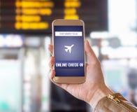 Incorporar en línea con el teléfono móvil en aeropuerto Incorporación de la mujer al vuelo con smartphone en el web Fotos de archivo libres de regalías