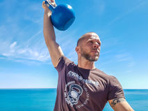 Incorrect Kettlebell Noob Grip. Taco Fleur from Cavemantraining demonstrates the incorrect noob grip on a kettlebell. Background shows the Mediterranean sea on royalty free stock photos