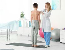 Incorrect posture concept. Physiotherapist examining and correcting. Boy`s back royalty free stock images