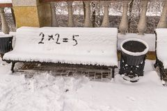 Incorrectly resolved mathematical example recorded on a snow. Covered bench Royalty Free Stock Photography