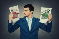 Increase and decrease. Surprised young accountant holding two papers in his hands with different graphs, looking shocked at the negative infographic. Colorful Stock Images