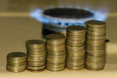 Increase in gas price concept. Blue gas flame and increasing stack of coins. royalty free stock photography