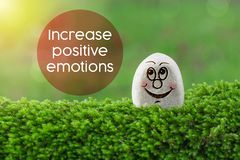 Increase positive emotions. The text Increase positive emotions with stone smile happy face on green moss and sunshine light background royalty free stock photo