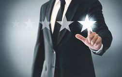 Increase ranking and rating with businessman is touching virtual screen.  stock photography