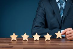 Increase rating five stars. Increase rating, evaluation and classification concept. Businessman sitting behind a table and add fifth wooden star royalty free stock images