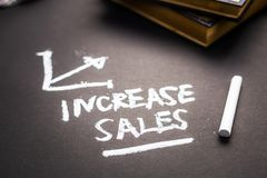 Increase Sales Note. Increase Sales handwriting note by chalk on black paper with part of books royalty free stock photos