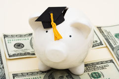 Increased Education Costs. A piggy bank wearing a graduation cap with hundred dollar bills on a beige background, increased education costs Stock Image