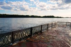 Increased water level. Flooded pier, abundance of precipitation, crowded river, global warming, the effects of glacial melting, ecology, ecological balance Stock Photo