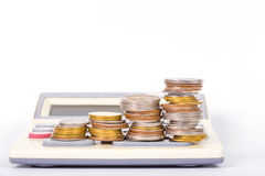 Increasing columns of coins, piles of coins arranged as a graph. Savings, increasing columns of coins, piles of coins arranged as a graph and calculator on white Stock Photos
