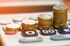 Increasing columns of gold coins arranged as a graph on calculat Stock Photo