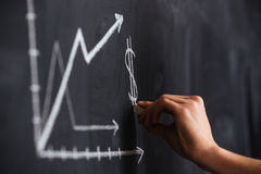 Increasing graph of currency rate drawn by hand on blackboard. With chalk Stock Photo
