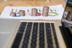 Increasing pile of coins on graph and chart. financial growth, i. Computer and increasing pile of coins on graph and chart. financial growth, income, investment Royalty Free Stock Photos