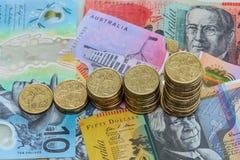 Increasing stacks of Australian Dollar coins. Australian one dollar coin stacks of increasing size on various Australia Dollar notes Royalty Free Stock Images