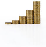 Increasingly higher stacks of gold coins on a white. Background Royalty Free Stock Image