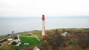 Incredible aerial panning shot of beautiful old lighthouse and buildings around on picturesque sea shore on overcast day stock video footage