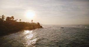 Incredible aerial shot of beautiful sunset ocean coastline, waves reflecting setting sun, reaching exotic tropical shore. Incredible aerial shot of beautiful stock video footage