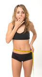 Incredible diet success. Astonished slim woman measuring her waist royalty free stock photography