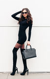 An incredible fashionable long-legged brunette girl in sunglasses with long hair dressed in a short black dress, black Royalty Free Stock Photos