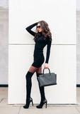An incredible fashionable long-legged brunette girl in sunglasses with long hair dressed in a short black dress, black Royalty Free Stock Photography