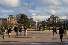 Incredible France. Paris, France, January 13, 2014. People enjoy their leisure time close to Arc de Triomphe du Carrousel and Louvre after the rain Royalty Free Stock Photos